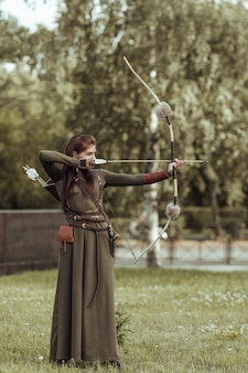 Young woman warrior with a bow pulls the bowstring with an arrow