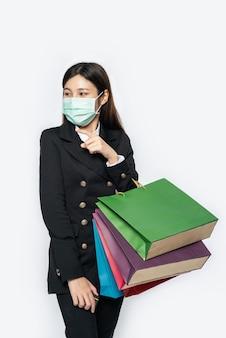 La giovane donna era vestita di scuro con una maschera e portava una borsa per fare acquisti
