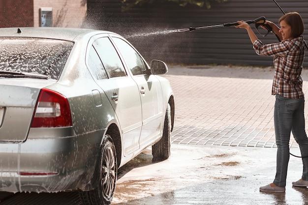 Молодая женщина моет машину на автомойке самообслуживания