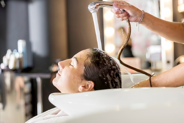 Young woman washing hair in salon
