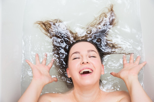 Young woman washing hair. shampoo and foam on black woman's hair.