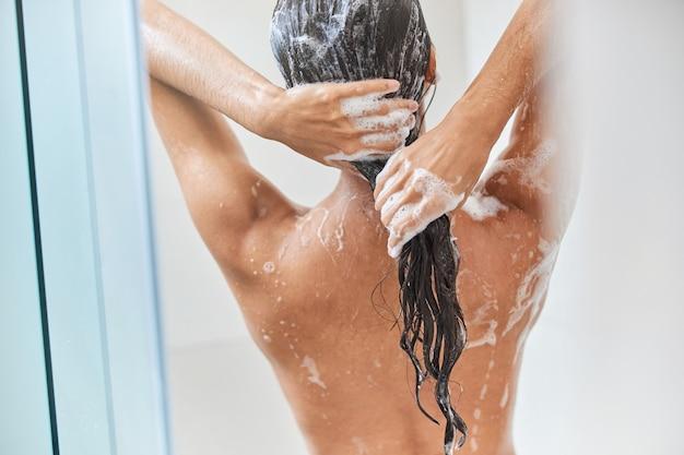 Молодая женщина моет волосы шампунем в душе