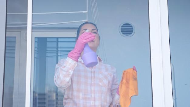 Молодая женщина моет окно в перчатках тряпкой,