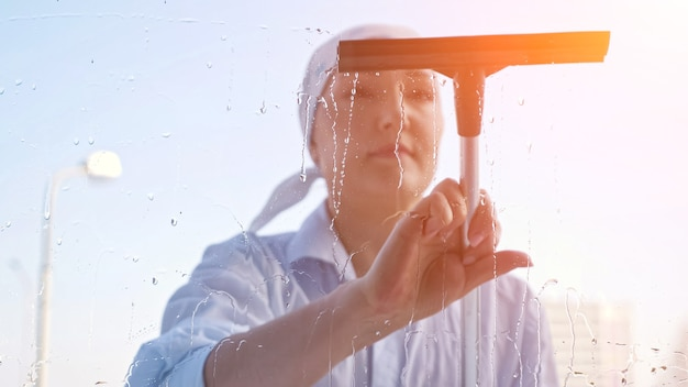 Young woman washing the window with a scraper