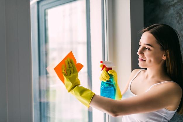 窓を洗う若い女性