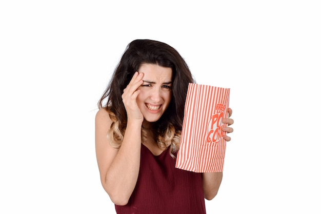 怖い映画を見ているとポップコーンを食べる若い女性。