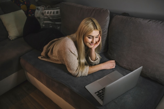 Young woman watching at laptop on sofa