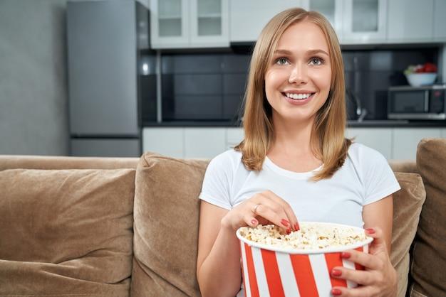Молодая женщина смотрит фильм и ест попкорн дома