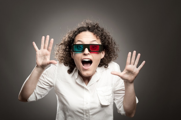 Young woman watching a movie wearing 3d glasses
