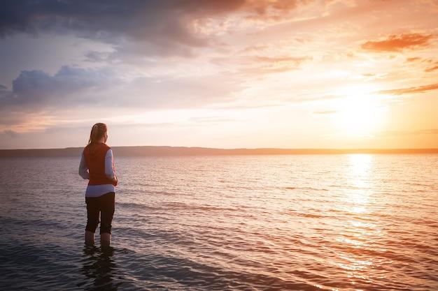 바다 일출을 보는 젊은 여자