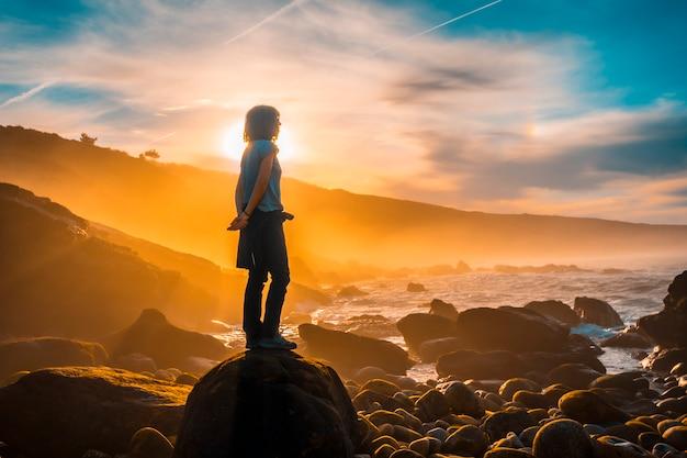A young woman watching the sea at sunset on the coast of jaizkibel near san sebastian. basque country