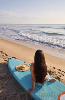 Молодая женщина наблюдает за волнами, сидя на песке с веслом