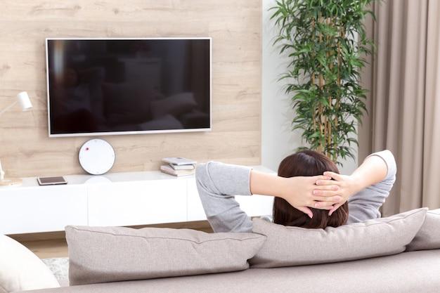 部屋でテレビを見ている若い女性