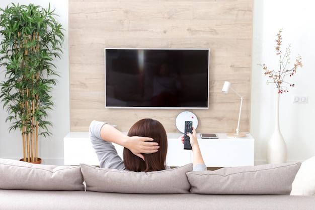 방에있는 Tv를보고 젊은 여자 프리미엄 사진