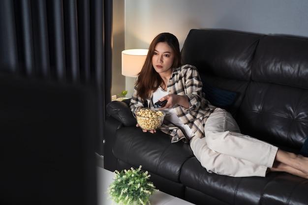 Молодая женщина смотрит телевизор на диване ночью