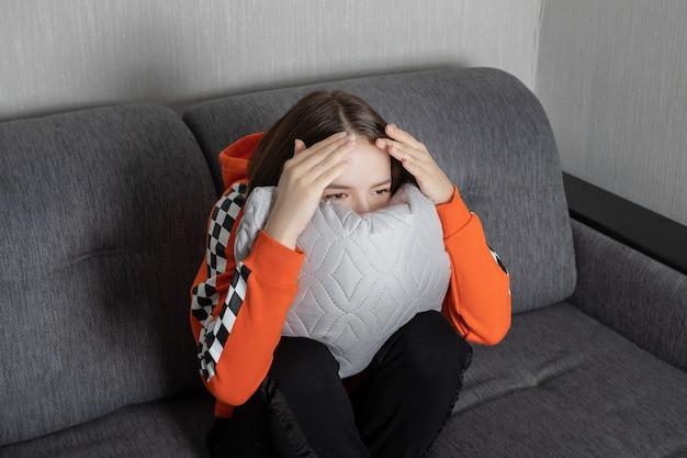 Young woman watching tv, sitting afraid, hiding