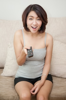 Young woman watching tv with remote control