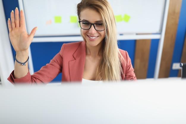 사무실에서 컴퓨터 화면에서 손을 흔들며 젊은 여자