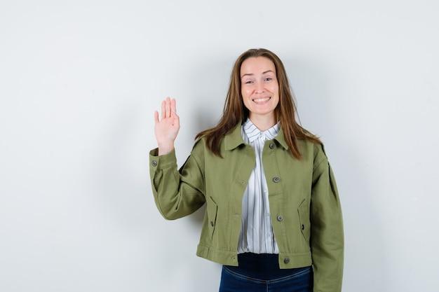 シャツ、ジャケット、陽気に見える、正面図で挨拶のために手を振っている若い女性。