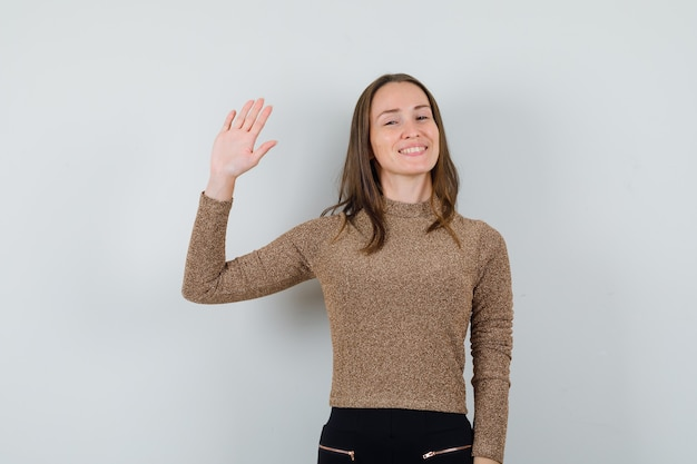 Young woman waving hand for goodbye in golden blouse and looking focused