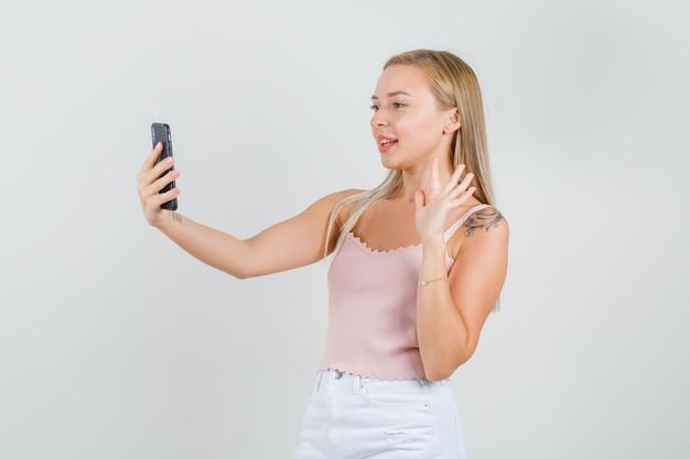 一重項でビデオ通話に手を振っている若い女性