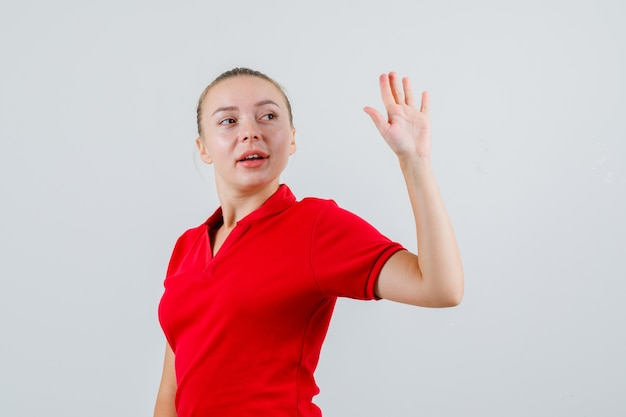 Young woman waving hand while looking back in red t-shirt and looking merry