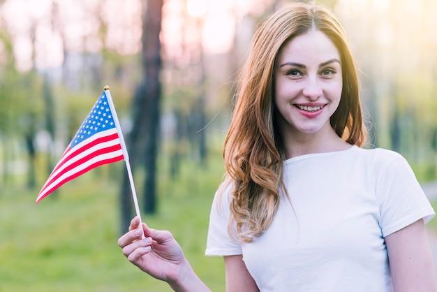 Молодая женщина развевает сувенирный флаг сша