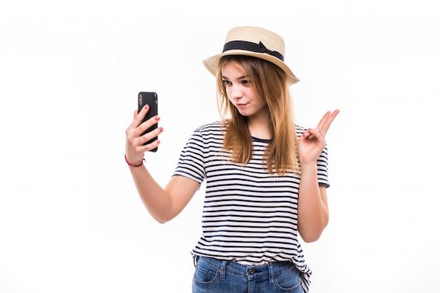 Usura della giovane donna in cappello di paglia e occhiali da sole che fanno una videochiamata