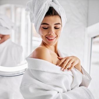 그녀의 머리에 목욕 가운과 수건을 입고 젊은 여자