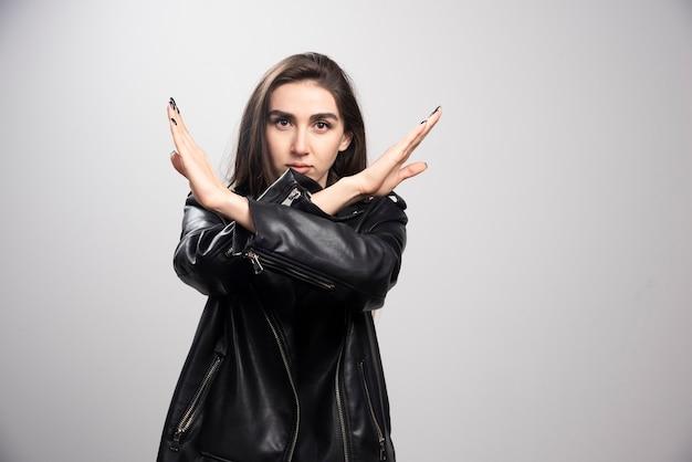 否定的なジェスチャーをしている黒い革のジャケットを着ている若い女性