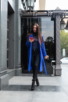 파란 코트를 입은 젊은 여성이 커피를 마시며 거리에서 전화 통화를 하고 있다. 락다운된 실시간 미디엄 샷