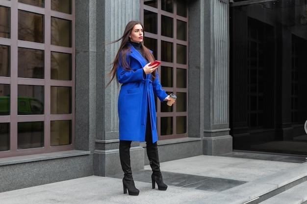 블루 코트를 입은 젊은 여성이 커피를 마시고 길거리에서 전화로 이야기하고 있습니다.