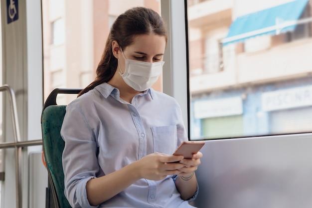 フェイスマスクを着用し、公共交通機関で旅行中に電話でチャットの若い女性