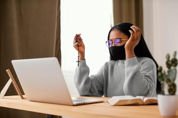 Молодая женщина в маске для лица во время молитвы