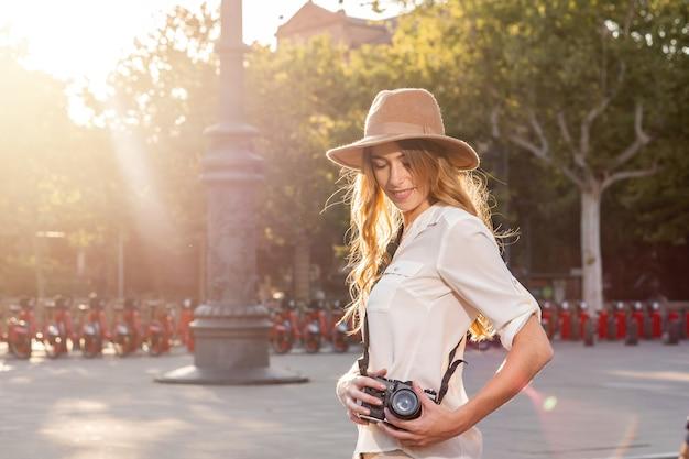 Молодая женщина в шляпе-федоре с фотоаппаратом