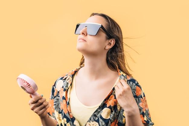 Молодая женщина в цветочной рубашке и больших солнцезащитных очках держит электрический вентилятор