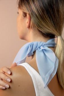 首のアクセサリーとしてハンカチを身に着けている若い女性