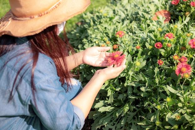 庭の花を気遣う帽子をかぶった若い女性。