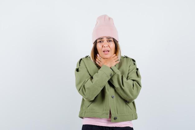 喉が痛いジャケットを着た若い女性