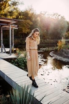 湖のほとりの木製の橋の上を歩く長いシフォンドレスを着て若い女性