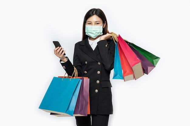 마스크를 착용하고 그녀의 스마트 폰에서 쇼핑 젊은 여자