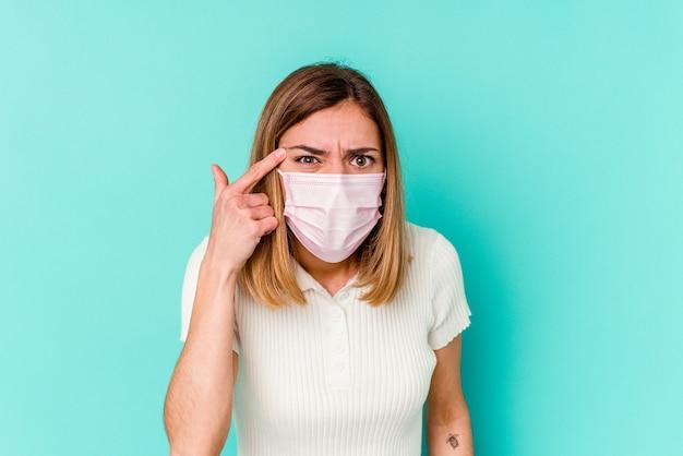 人差し指で失望のジェスチャーを示す青い背景に分離されたウイルスのマスクを身に着けている若い女性。