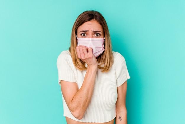 Молодая женщина в маске от вируса, изолированного на синих кусающих ногтях, нервничает и очень тревожится.