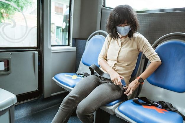 마스크를 쓰고 젊은 여자가 버스를 타기 전에 안전 벨트를 고정하는 동안 벤치에 앉아