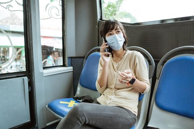 마스크를 쓰고 젊은 여자는 도중에 버스에서 전화를하는 동안 벤치에 앉아