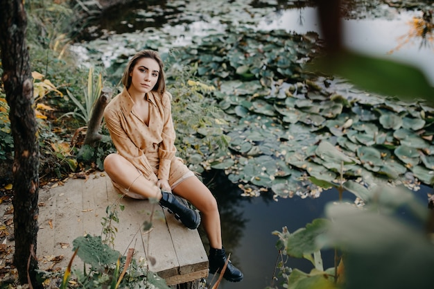 睡蓮と湖のそばの木製の桟橋に座っているマキシシフォンドレスを着て若い女性
