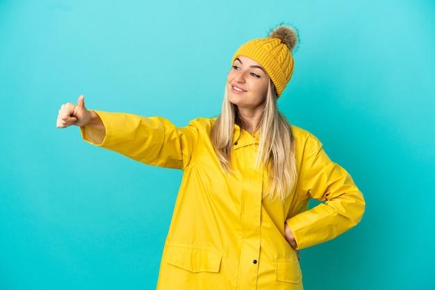 Молодая женщина в непромокаемом пальто на синем фоне показывает палец вверх