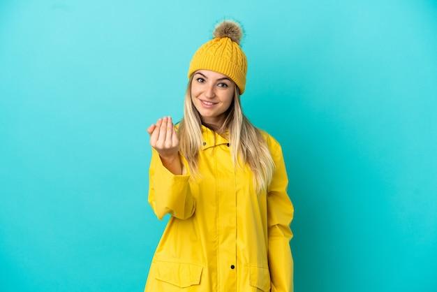 孤立した青い背景の上に防雨コートを着て、手で来るように誘う若い女性。あなたが来て幸せ