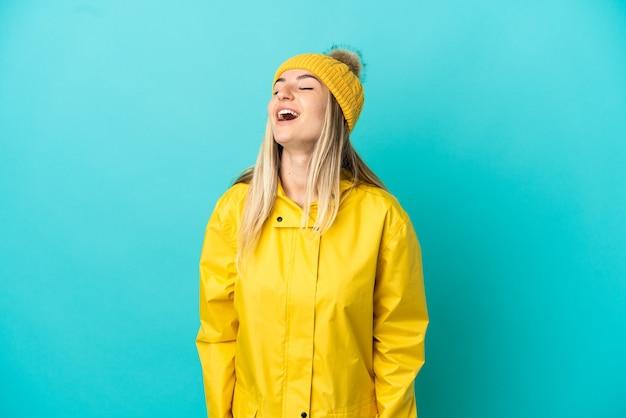 笑っている孤立した青い背景の上に防雨コートを着ている若い女性