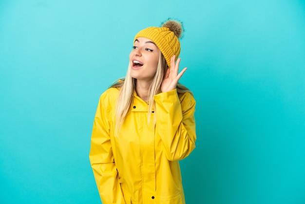 耳に手を置くことによって何かを聞いて孤立した青い背景の上に防雨コートを着ている若い女性